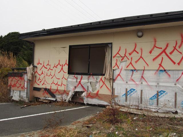 富岡駅前。津波で流された家が道路の上に。無数の「人」の落書きがそこら中に書かれている。